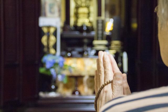 仏壇に手を合わす老人